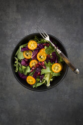 Bowl of mixed green salad with red cabbage, kumquat and pomegranate seeds - LVF07260