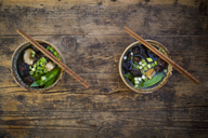 Two bowls of Japanese miso soup with sugar peas, shitake mushrooms, tofu and mung sprouts - LVF07275
