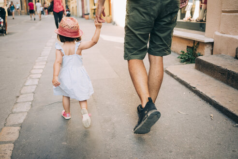 France, Aix-en-Provence, toddler girl and father walking hand in hand in the city - GEMF02111