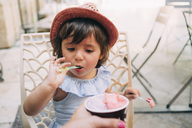 Cute toddler girl eating an ice cream held by her mother - GEMF02114