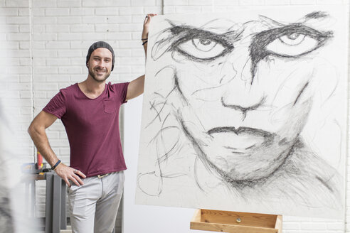 Portrait of confident artist with drawing in studio - ZEF15852
