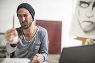 Artist sitting at his desk in studio checking pencil - ZEF15870