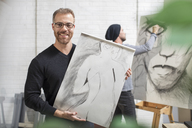 Smiling man holding drawing in artist's studio - ZEF15876