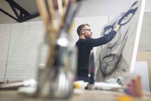 Man checking drawing in studio - ZEF15882
