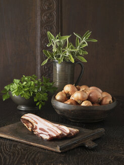 Ingredients to make stuffing. Pancetta, brown onions, parsley and sage on rustic wooden surface - CUF41160