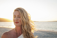 Blond woman with eyes closed on beach at dusk, Cape Town, South Africa - CUF41325