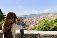 Young female tourist looking through coin operated binoculars in Lisbon, Portugal - CUF41328