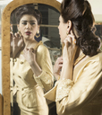 Close up of woman in vintage clothes looking in mirror - CUF41346