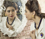 Woman in vintage clothes looking in mirror - CUF41349