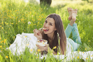 Woman in field of buttercups eating fresh fruit - CUF41361