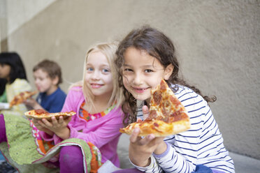 Small group of children eating pizza outdoors - CUF41472
