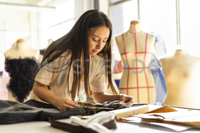Young fashion designer working in her studio - AFVF00749