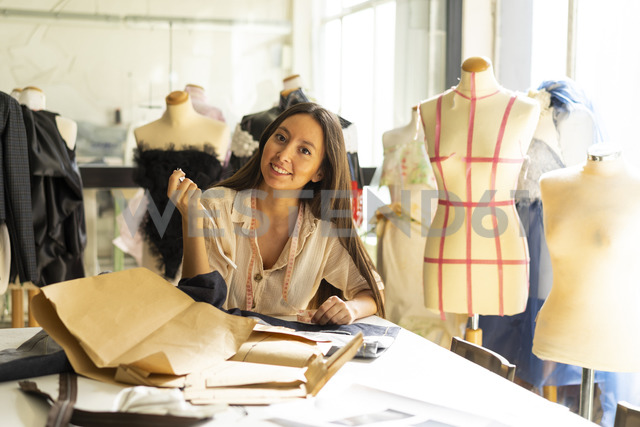 Young fashion designer working in her studio - AFVF00752