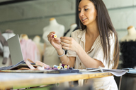 Young fashion designer working in her studio - AFVF00761