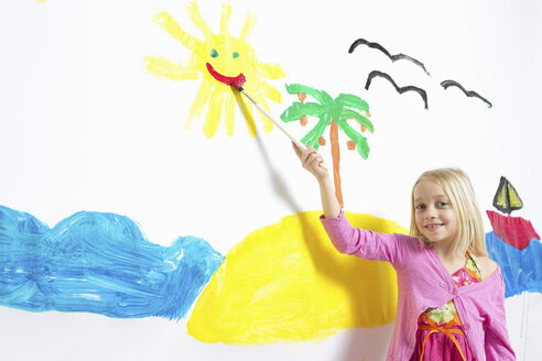 Young girl painting smiling sunshine face on wall - CUF41497