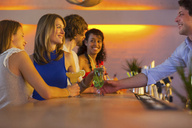 Group of friends ordering cocktails in bar - CUF41506