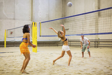 Friends playing indoor beach volleyball - CUF41524