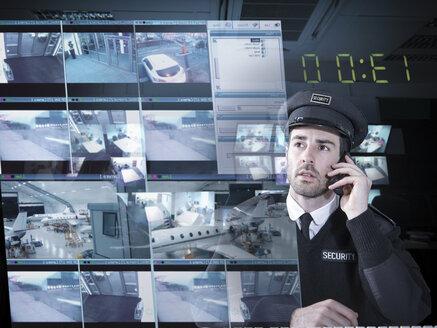 Security guard monitoring camera visuals on interactive screen - CUF41569