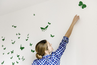 Young woman decorating wall with green butterflies - CUF41591