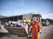 Portrait of worker in reflective workwear with dumper of crushed titanium - CUF41597