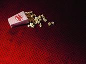 Spilled carton of popcorn on cinema carpet - CUF41793