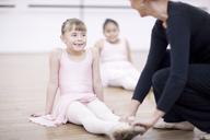Teacher adjusting feet position of young ballerina - CUF41916