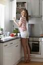 Woman taking mug from cabinet - CUF42078