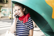 Young woman using pay telephone - CUF42288