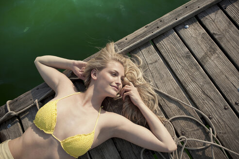 Young woman lying on pier - CUF42336