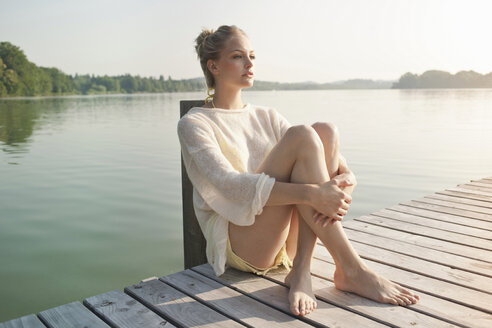 Young woman sitting on lake pier - CUF42351