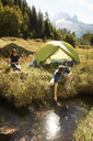Couple camping by stream, Chamonix, Haute Savoie, France - CUF42378