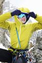 Mid adult woman adjusting ski goggles - CUF42405