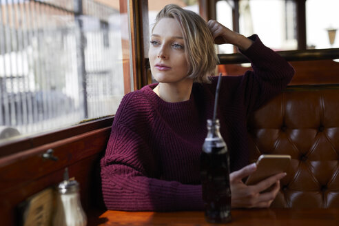 Portrait of blond woman in a cafe looking out of window - PNEF00719