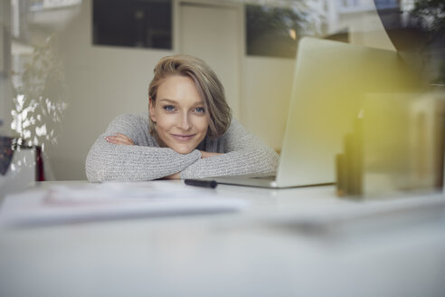 Portrait of smiling young woman leaning on desk with laptop - PNEF00731