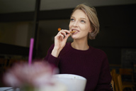Portrait of blond woman in a cafe eating a cookie looking away - PNEF00743
