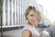 Portrait of happy blond woman with takeaway coffee in the city - PNEF00746