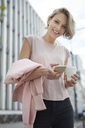Portrait of happy blond woman with takeaway coffee and cell phone in the city - PNEF00749