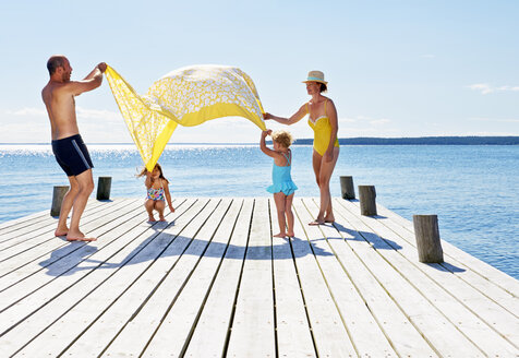 Parents and two young girls playing on pier, Utvalnas, Gavle, Sweden - CUF42674