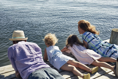 Parents and daughters lying on pier, Utvalnas, Gavle, Sweden - CUF42677