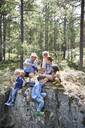 Family sitting on rocks in forest eating picnic - CUF42689