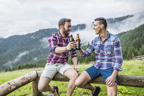 Two male friends drinking beer on fence, Tyrol Austria - CUF42823