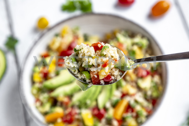 Spoon of bulgur salad with bell pepper, tomatoes, avocado, spring onion and parsley - SARF03832