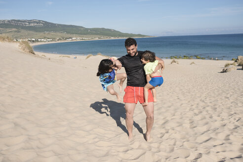 Father playing with his son and daughter at the beach, having fun - JASF01892