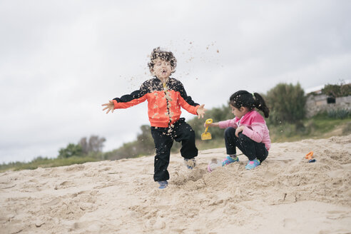 Brother and sister playing on the beach with sand - JASF01895