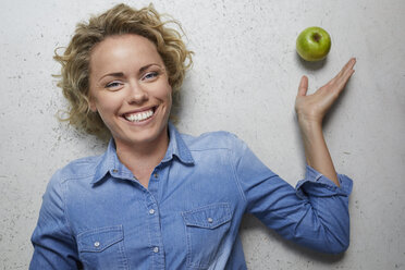 Portrait of happy blond woman with green apple - PNEF00755