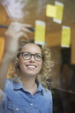 Portrait of smiling blond businesswoman looking at adhesive note on glass pane - PNEF00758