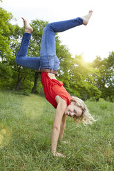 Portrait of happy blond woman doing handstand on a meadow - PNEF00761