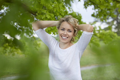 Portrait of relaxed blond woman with hands behind her head in nature - PNEF00764