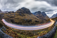 UK, Scotland, car light trails on scenic road through the mountains in the Scottish highlands near Glencoe at dusk - WPEF00686