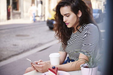 Young woman using cell phone at outdoor cafe in the city - ABIF00683